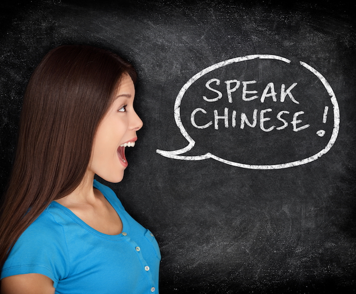 Chinese language learning concept. Woman speech bubble on blackboard saying SPEAK CHINESE. Fun happy mixed race student or teacher.