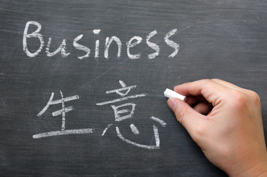 Business- word written on a smudged blackboard with a Chinese translation,with a hand holding chalk
